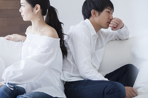 Young couple has turned their backs to each other sitting on the sofa